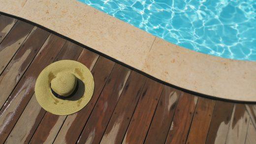 chapeau de paille posé à côté de la margelle de la piscine